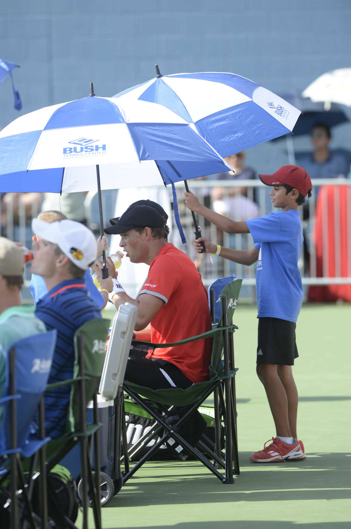 Mike and Bob Bryan cool off with some assistance from volunteer umbrella holders during the West Texas Tennis Classic on Saturday, Sept. 26, 2015, at Bush Tennis Center. James Durbin/Reporter-Telegram