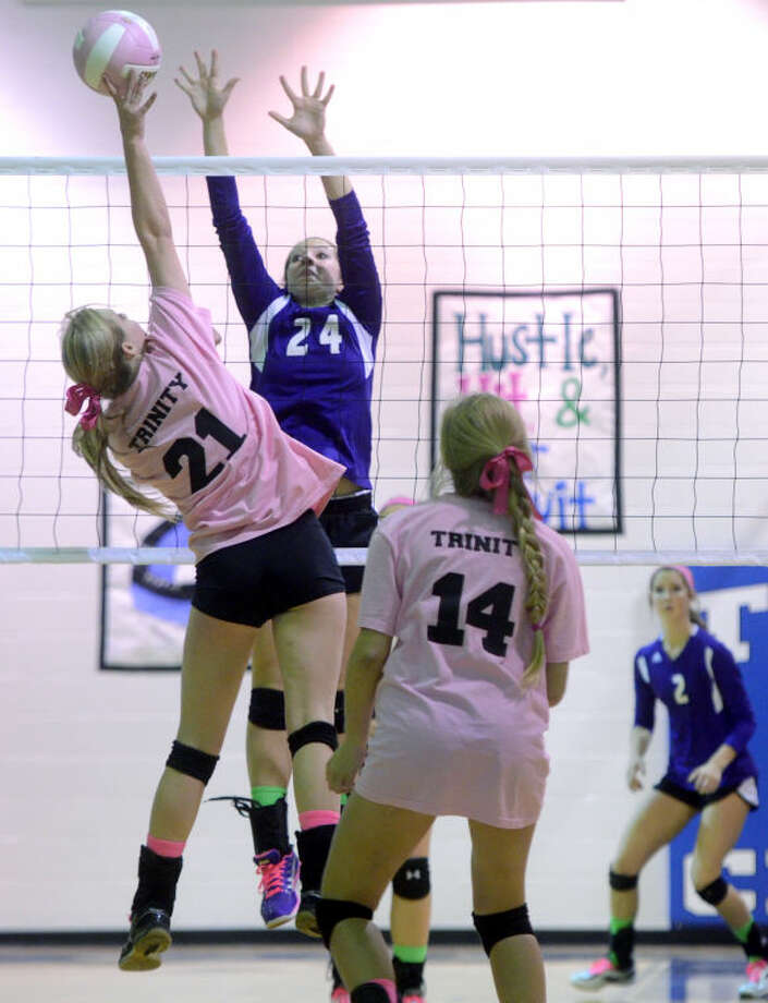 """Midland Classical's Alissa Beattie (24) tries to block a hit from Trinity's India Lewis (21) during Trinity's """"Dig Pink"""" game for breast cancer awareness Tuesday at Trinity School. James Durbin/Reporter-Telegram Photo: JAMES DURBIN"""