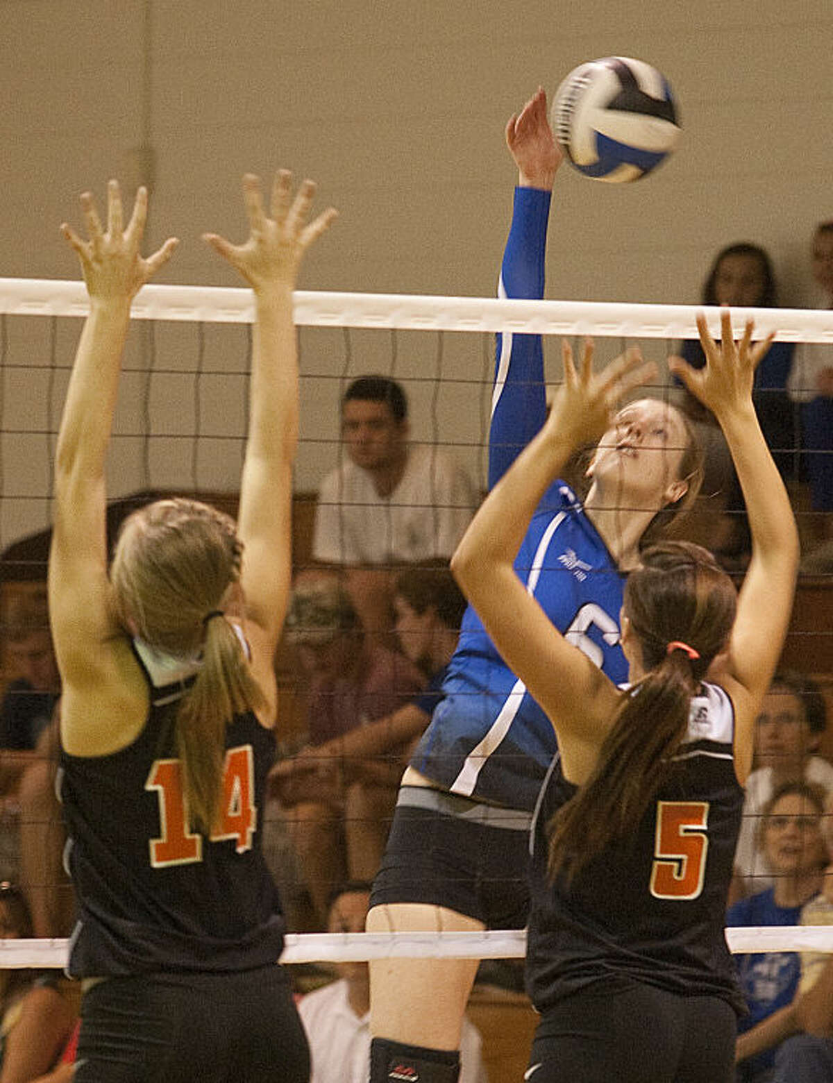 Trinity's Ashley Stroup attempts a spike as Wink's Michelle Halterman, 14 and Tawny Underwood, 5, go for a block Friday evening at Trinity. Tim Fischer\Reporter-Telegram
