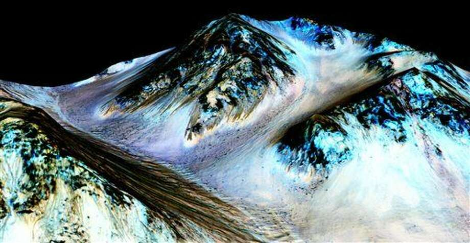 This undated photo provided by NASA and taken by an instrument aboard the agency's Mars Reconnaissance Orbiter shows dark, narrow, 100 meter-long streaks on the surface of Mars that scientists believe were caused by flowing streams of salty water. Researchers said Monday, Sept. 28, 2015, that the latest observations strongly support the longtime theory that salt water in liquid form flows down certain Martian slopes each summer. (NASA/JPL/University of Arizona via AP) Photo: HOGP