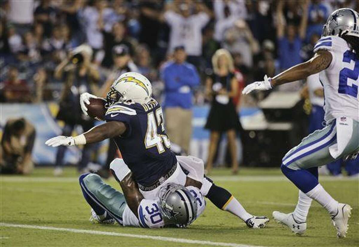 San Diego Chargers running back Branden Oliver struggles past Dallas Cowboys cornerback Terrance Mitchell while scoring a touchdown during the first half of a preseason NFL football game Thursday, Aug. 7, 2014, in San Diego. (AP Photo/Jae C. Hong)