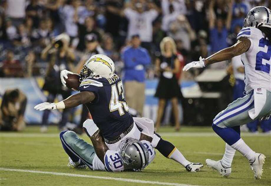 San Diego Chargers running back Branden Oliver struggles past Dallas Cowboys cornerback Terrance Mitchell while scoring a touchdown during the first half of a preseason NFL football game Thursday, Aug. 7, 2014, in San Diego. (AP Photo/Jae C. Hong) Photo: Jae C. Hong
