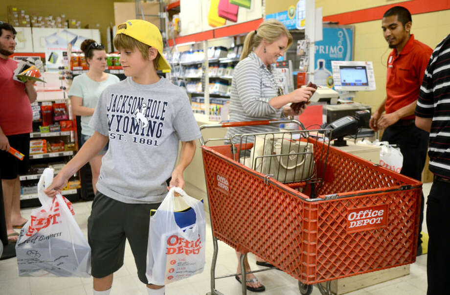 Jase Brooks, an 8th grader at Abell Junior High, carries school supplies while his mother Cara pays during tax-free weekend Friday at Office Depot. James Durbin/Reporter-Telegram