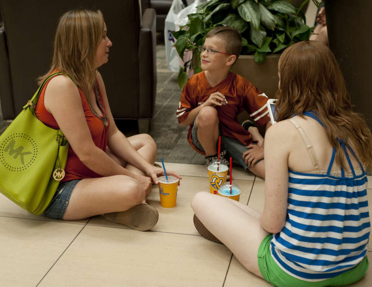 Toni Thompkins sits with her children, Kyle and Mackenzie, as they take a break from shopping Friday at Midland Park Mall. Tim Fischer\Reporter-Telegram