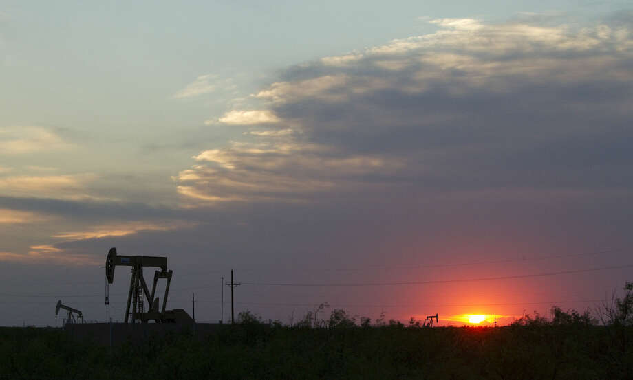 The sun sets behind a group of pump jacks Wednesday, June 1, 2011, outside of Midland. ( Brett Coomer / Houston Chronicle ) Photo: Brett Coomer