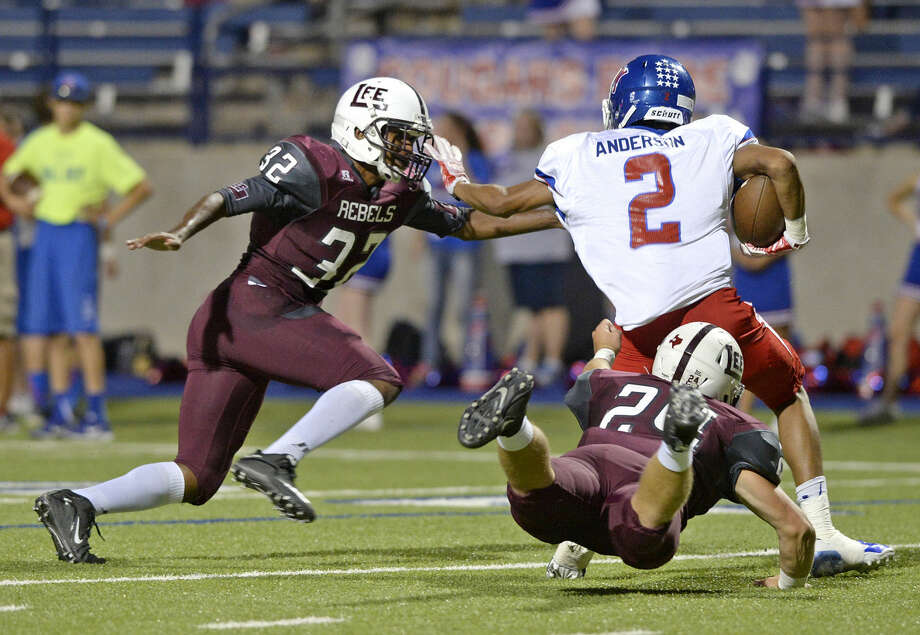 Lee High defensive back Conner Friel (32) and linebacker Austin McClure (24) tackle Abilene Cooper wide receiver Aaron Anderson (2) on Friday, Sept. 25, 2015, at Grande Communications Stadium. James Durbin/Reporter-Telegram Photo: James Durbin
