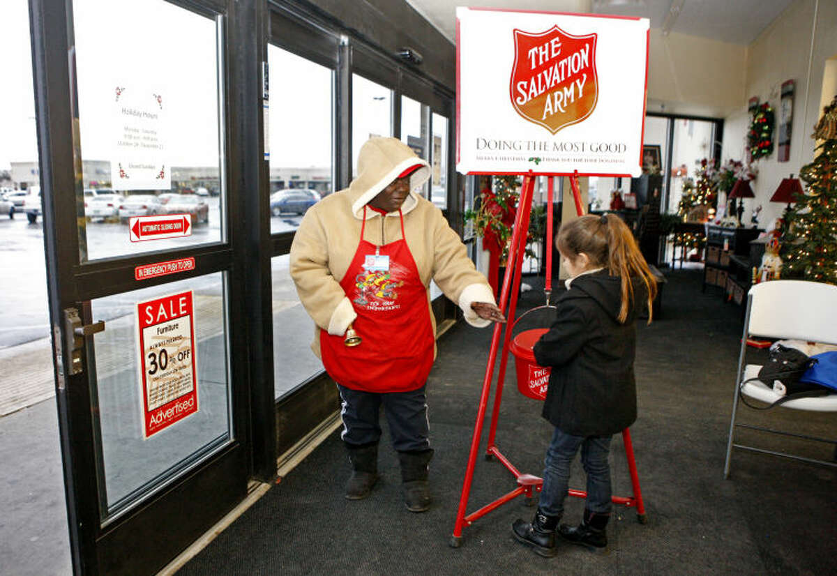 In this file photo, Salvation Army of Midland bell-ringer Vickie McGrew accepts a donation from Laura Worsham, age 6, at Hobby Lobby on Thursday. James Durbin/Reporter-Telegram