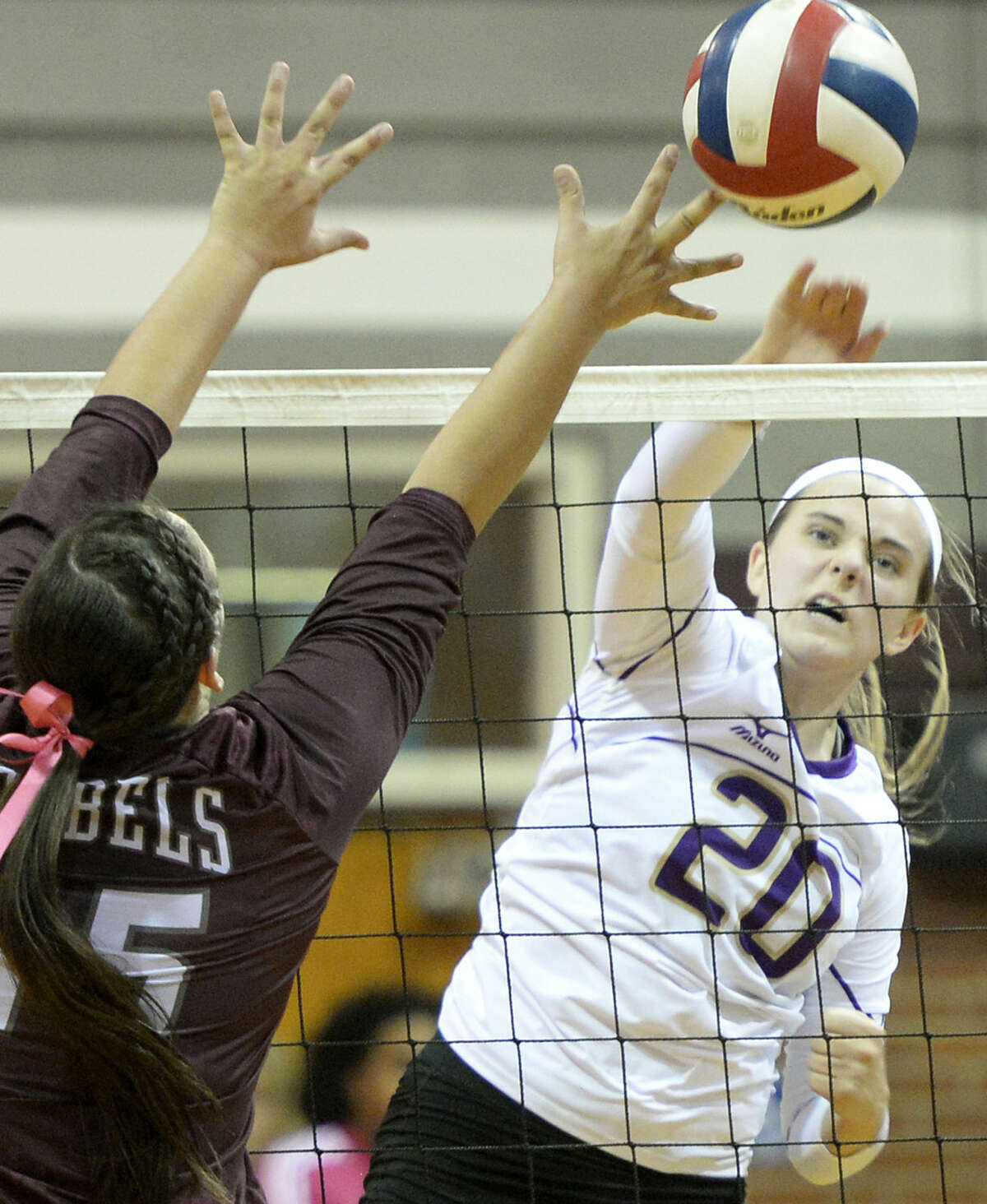 Midland High outside hitter Claire Lancaster (20) delivers a kill shot past Lee High's Alissa Erdwurm (15) on Friday, Oct. 2, 2015 at Lee High. James Durbin/Reporter-Telegram