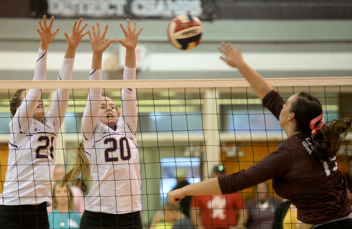 Midland High middle hitter Krista Epley (21) and outside hitter Claire Lancaster (20) block a hit from Lee High's Alissa Erdwurm (15) on Friday, Oct. 2, 2015 at Lee High. James Durbin/Reporter-Telegram