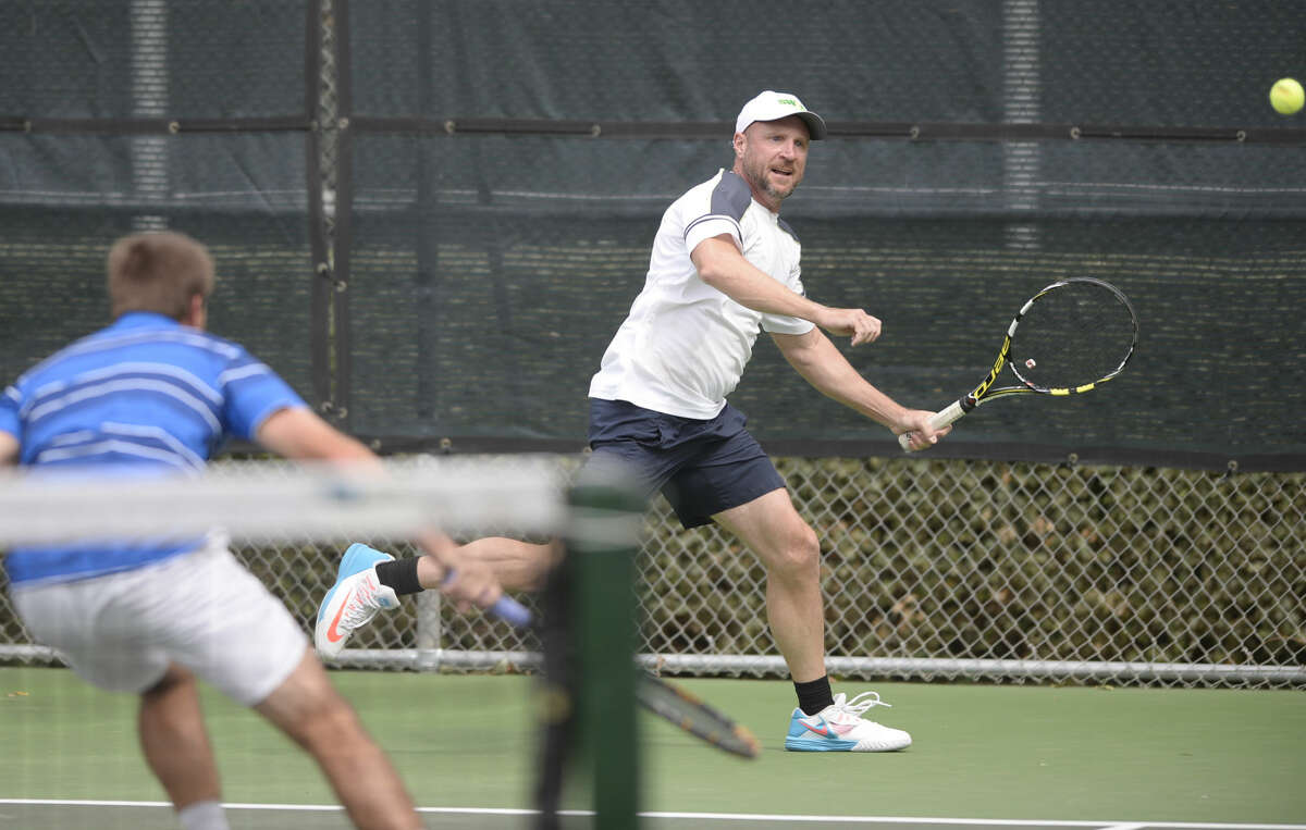 Luke Morrow returns a hit as teammate Jeremy Earl (blue shirt) looks on during a doubles match in the Southwest Oilman's Tennis Tournament on Saturday, Oct. 3, 2015, at Midland Country Club. James Durbin/Reporter-Telegram