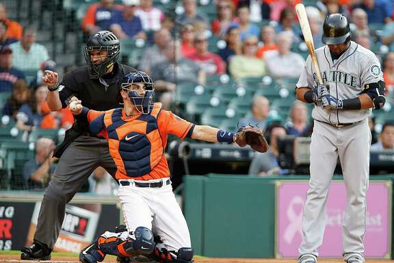 Houston Astros catcher Jason Castro center, throws the ball as umpire Manny Gonzalez left, makes a call and Seattle Mariners right fielder Nelson Cruz right, looks down during the first inning of MLB game action at Minute Maid Park Friday, May 6, 2016, in Houston.
