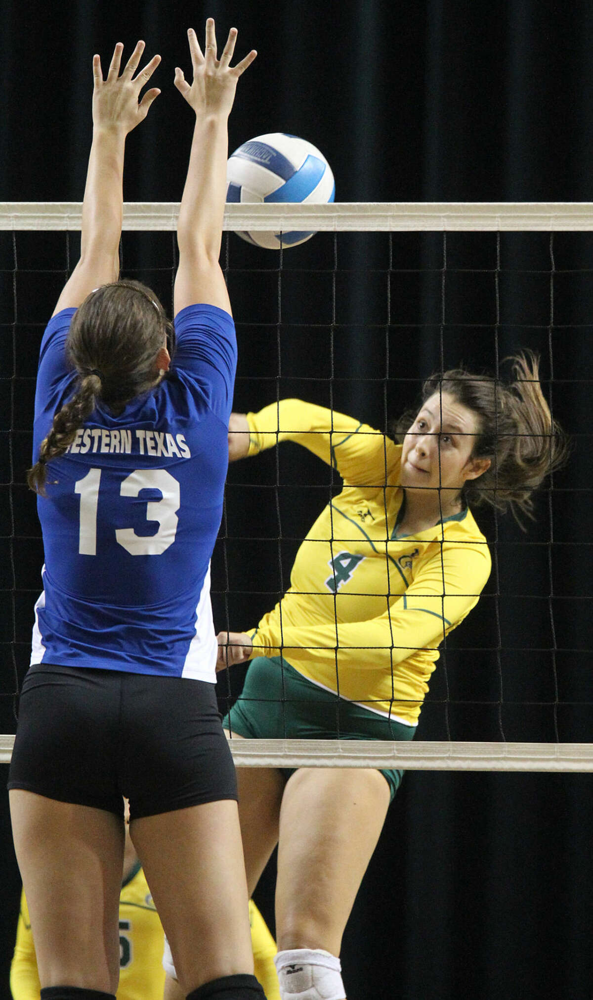 Midland College's Aleana Crow (4) hits against Western Texas College's Anamaurie Perkins (13) on Wednesday, Sept. 23, 2015 at Chaparral Center. James Durbin/Reporter-Telegram
