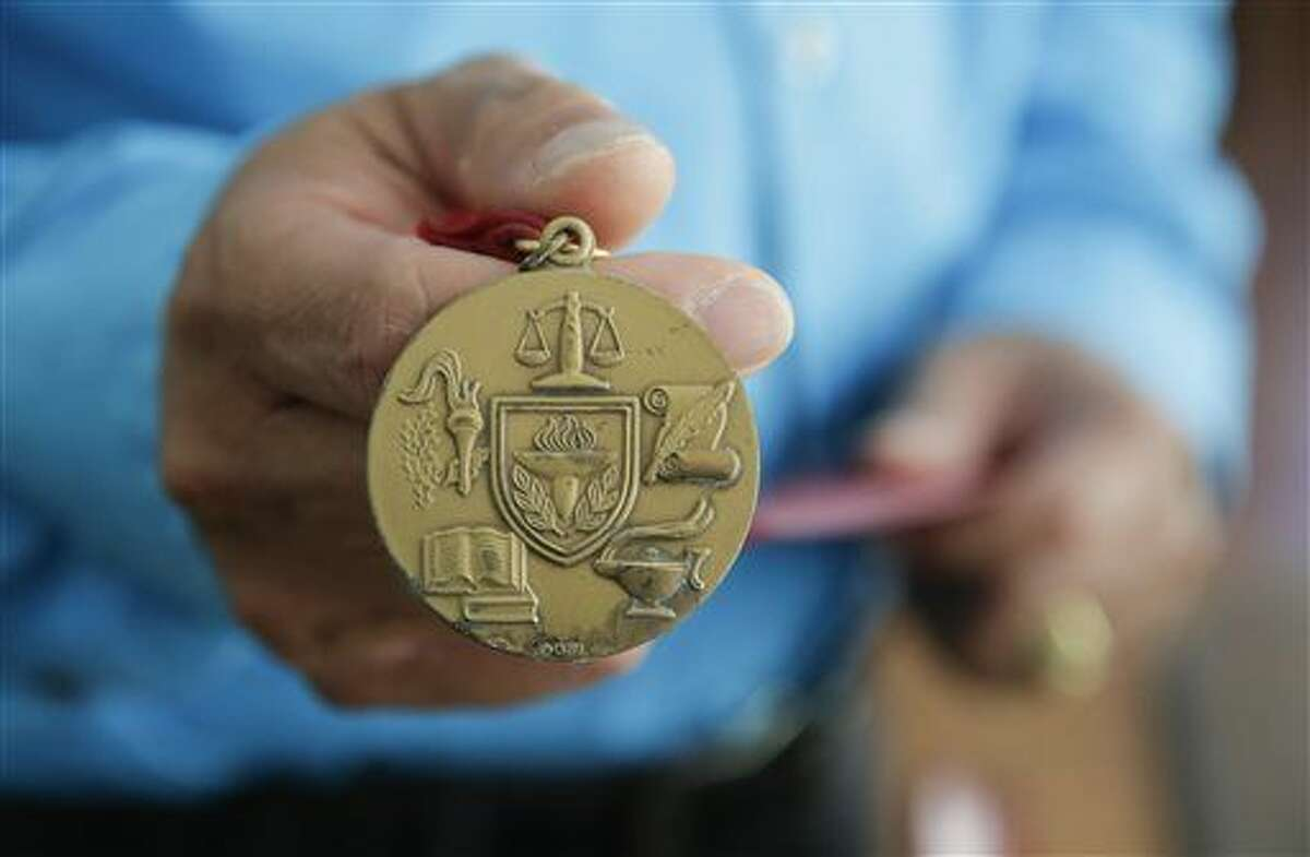 """In this July 10, 2015 photo, Ernie Rosales holds his summa cum laude medal from Azusa Pacific University at his home in Temecula, Calif. """"You reach a certain level in the corporate world you cannot go above without a bachelor's or master's,"""" explained Rosales. (AP Photo/Chris Carlson)"""