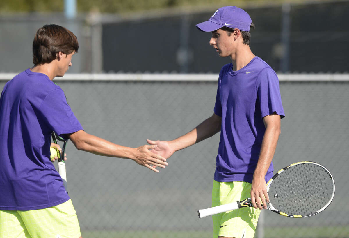 Midland High's Hayden Boldrick (right) and Brandt Schneider (left) shake hands while competing in a doubles match against Lee High on Tuesday, Oct. 6, 2015, at the Raquet Club. James Durbin/Reporter-Telegram