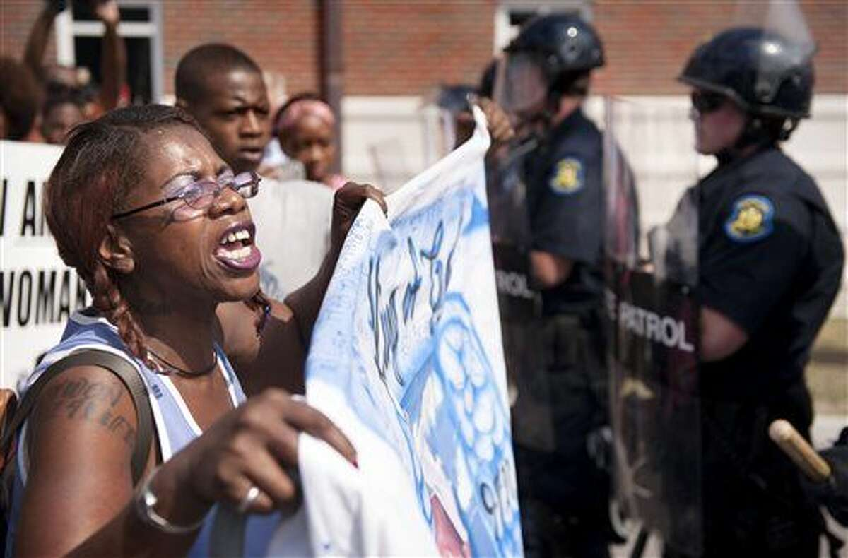 Marcelle Stewart, left, confronts police officers during a march and rally in downtown Ferguson, Mo., Monday, Aug. 11, 2014. The group marched along the closed street, rallying in front of the town's police headquarters to protest the shooting of 18-year-old Michael Brown by Ferguson police officers. Brown, who was killed in a confrontation with police in the St. Louis suburb, was shot Saturday, Aug. 9, 2014, and died following the confrontation with police. Stewart said she was attending the rally because her son-in-law Jason Moore died after being shot with a taser by police. (AP Photo/Sid Hastings)