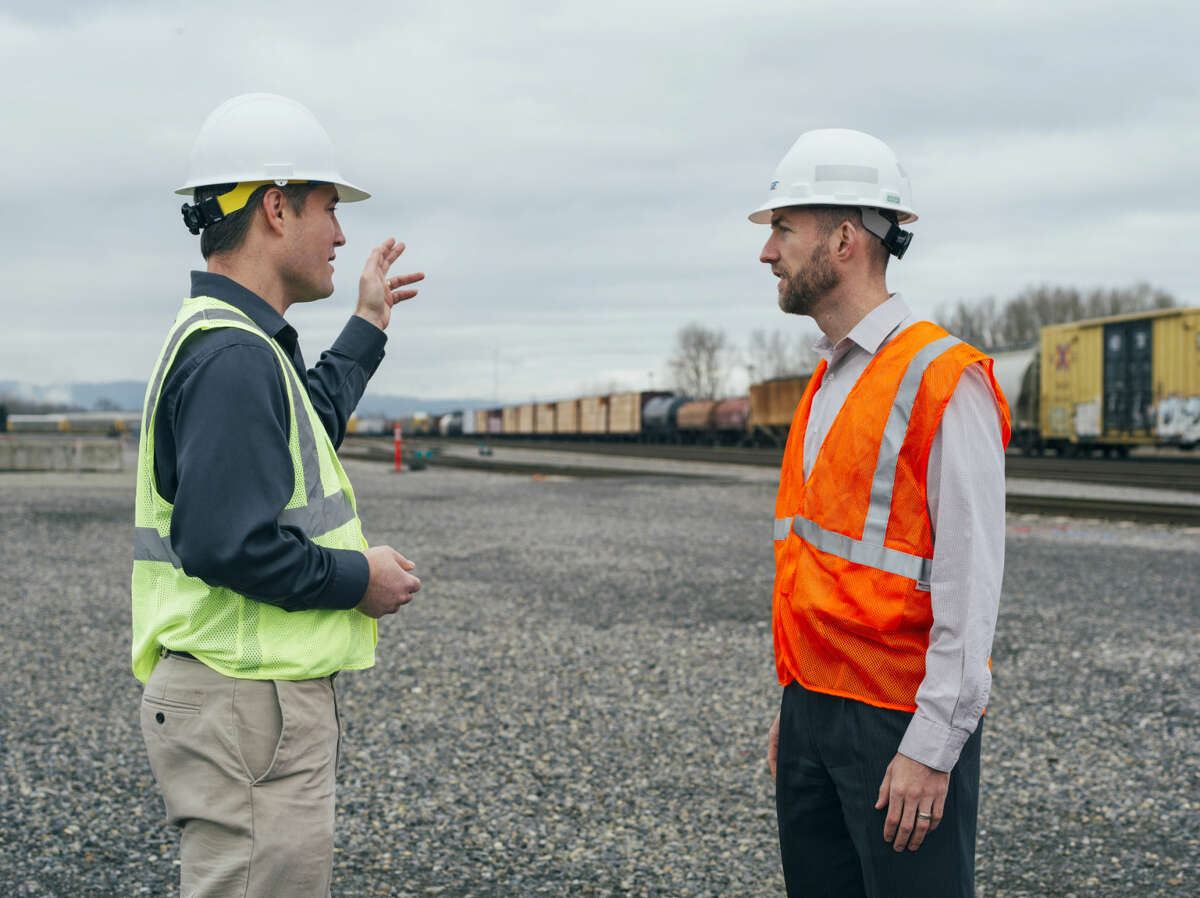 Jared Larrabee, right, the general manager of Vancouver Energy, speaks with Jeff Hymas, a consultant, on the site of a proposed oil shipment rail terminal in Vancouver, Wash., in this Dec. 16, 2014, file photo.