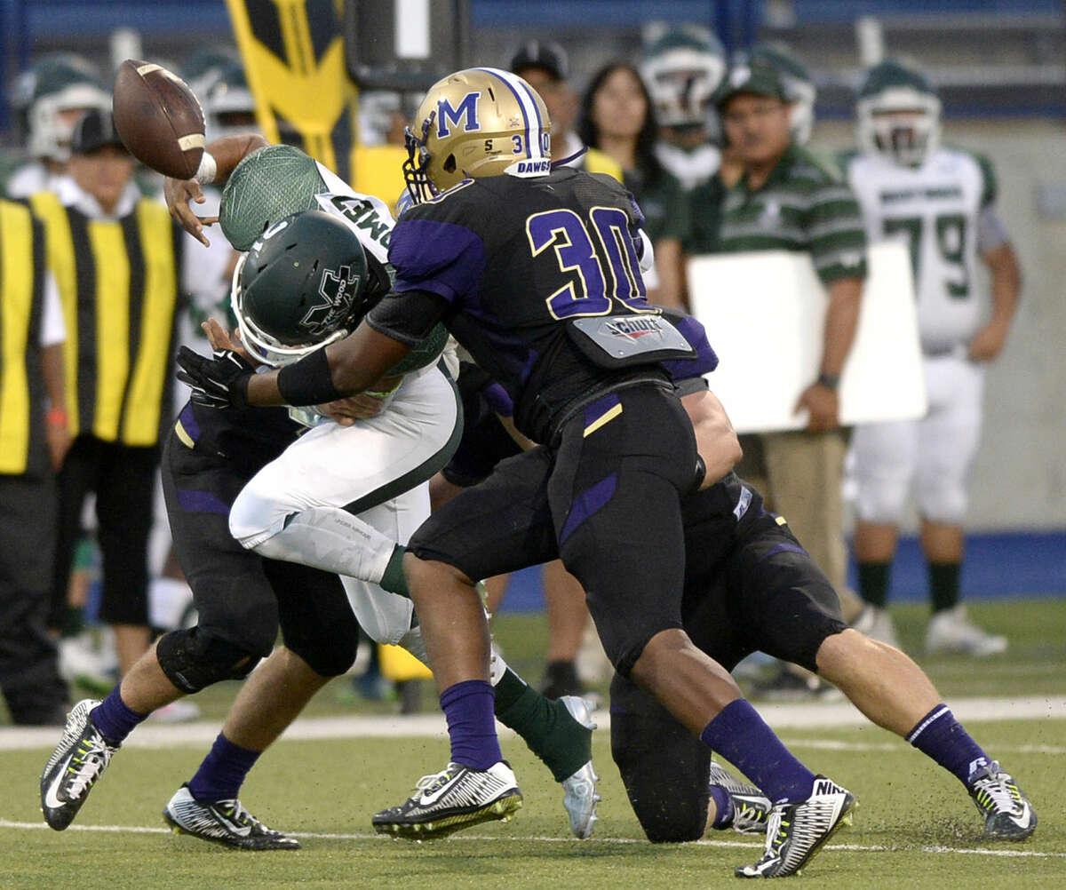 El Paso Montwood running back Brandon Gromez fumbles while being hit by Midland High safety Holt Wood (17), defensive end Willie Echols (30), and defensive end Traver Vliem (9) on Friday, Sept. 4, 2015, at Grande Communications Stadium. James Durbin/Reporter-Telegram