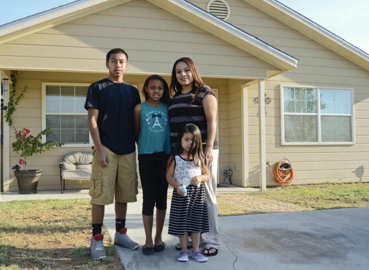 Habitat home owner Agatha Lopez with her children, Tony Zarate, Javen Polk and Aliyannah Cisneros. Tim Fischer\Reporter-Telegram