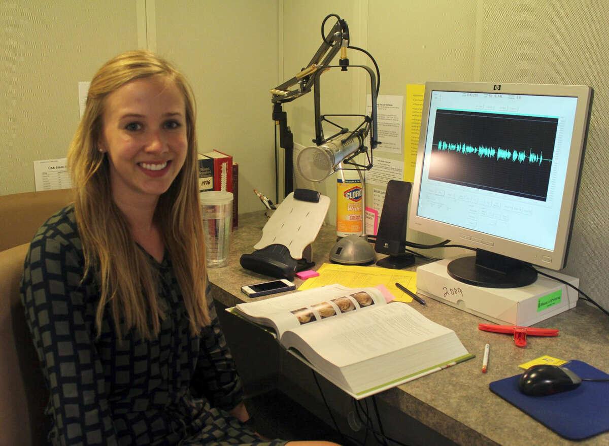 Junior League volunteer Stephanie Beckham records a text book.