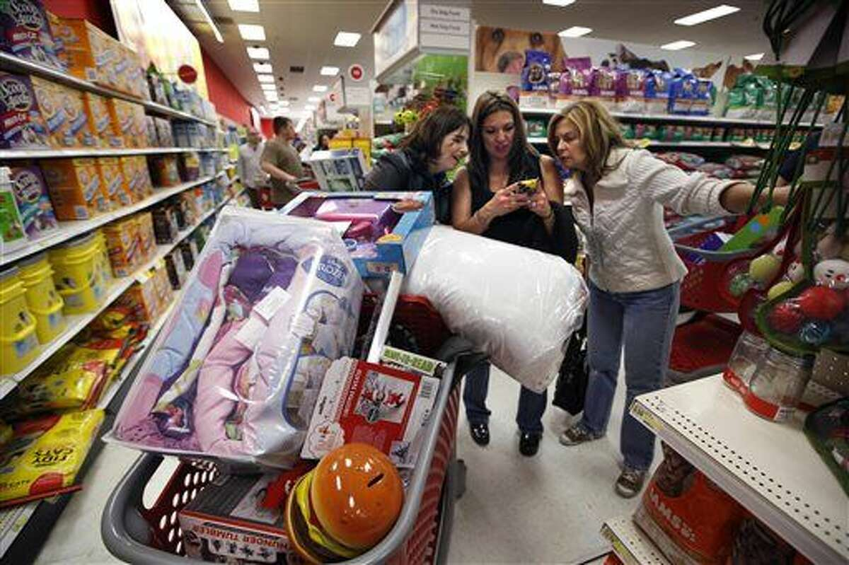 FILE - In this Nov. 28, 2014 file photo, Target shoppers Kelly Foley, left, Debbie Winslow, center, and Ann Rich use a smartphone to look at a competitor's prices while shopping shortly after midnight on Black Friday, in South Portland, Maine. Wal-Mart and Target, two of the biggest U.S. retailers, on Thursday, Oct. 29, 2015 rolled out plans to lure shoppers into stores during the holiday season by pushing discounts, free shipping and spiffed up stores. (AP Photo/Robert F. Bukaty, File)