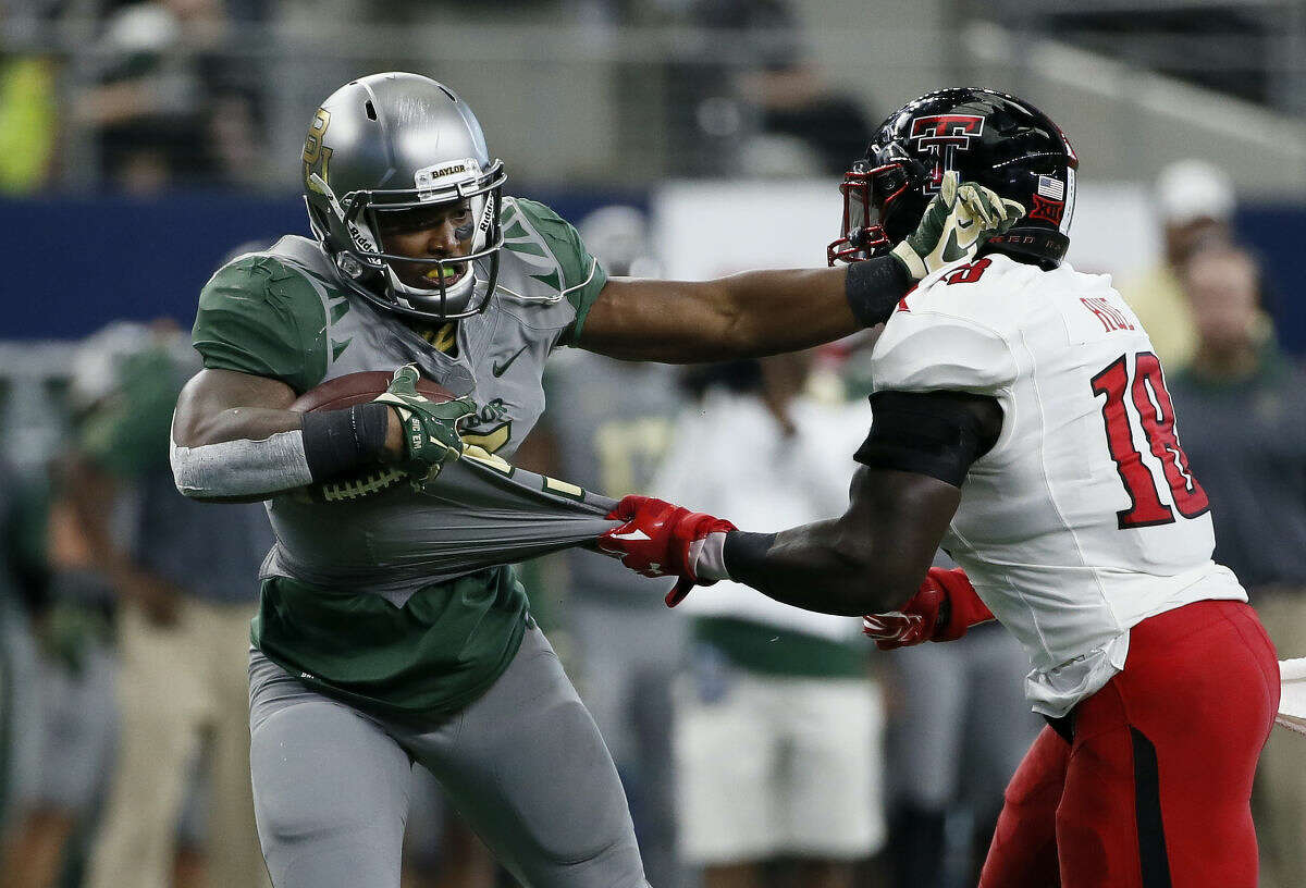 Baylor running back Johnny Jefferson, left, fights off a tackle attempt by Texas Tech linebacker Micah Awe (18) after grabbing a pass from quarterback Seth Russell in the second half of an NCAA college football game Saturday, Oct. 3, 2015, in Arlington, Texas. Baylor won 63-35. (AP Photo/Tony Gutierrez)