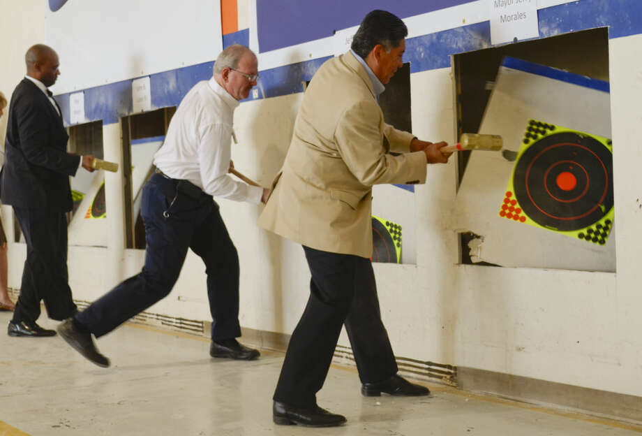 """Mayor Jerry Morales, XCOR CEO Jeff Greason, city councilman John Love III and others help """"break the walls"""" during a ceremony Friday at XCOR's hanger at MAF. Tim Fischer\Reporter-Telegram Photo: Tim Fischer"""