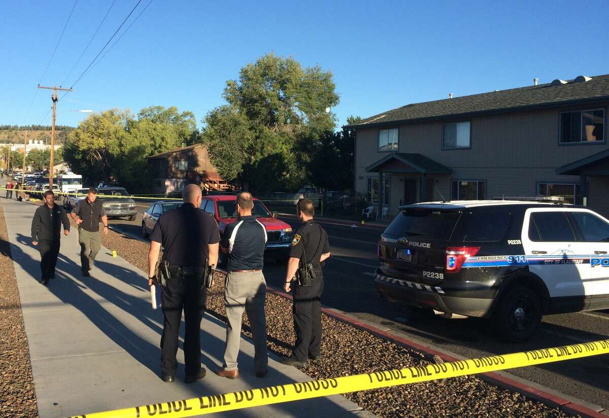 Authorities gather outside a student dormitory at Northern Arizona University in Flagstaff, Ariz., Friday after an early-morning fight between two groups of college students escalated into gunfire leaving one person dead and three others wounded, authorities said.