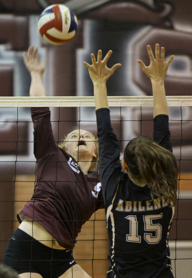 Lee High's Emily Hillman looks to spike the ball past Abilene High's London Moore Tuesday 10-6-2015 at Lee High. Tim Fischer\Reporter-Telegram