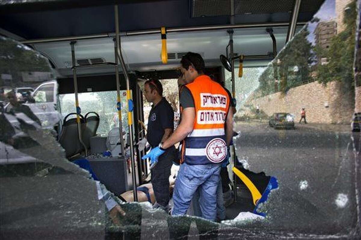 Israeli medics and police inspect the scene of a shooting attack in Jerusalem, Tuesday, Oct. 13, 2015. A pair of Palestinian men boarded a bus in Jerusalem and began shooting and stabbing passengers, while another assailant rammed a car into a bus station before stabbing bystanders, in near-simultaneous attacks that escalated a month long wave of violence. Two Israelis and one attacker were killed. (AP Photo/Oded Balilty)