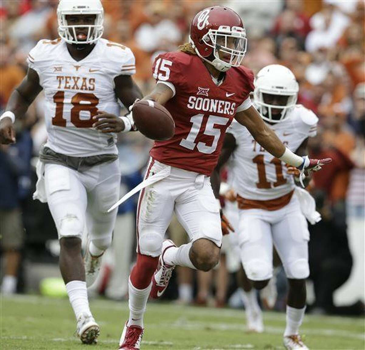 FILE - In this Oct. 11, 2014, file photo, Oklahoma cornerback Zack Sanchez (15) celebrates scoring a touchdown after intercepting a pass against Texas wide receiver Jacorey Warrick (11) and quarterback Tyrone Swoopes (18) during the first half of an NCAA college football game at the Cotton Bowl in Dallas. Texas and Oklahoma meet Saturday, Oct. 10, 2015. (AP Photo/LM Otero, FIle)