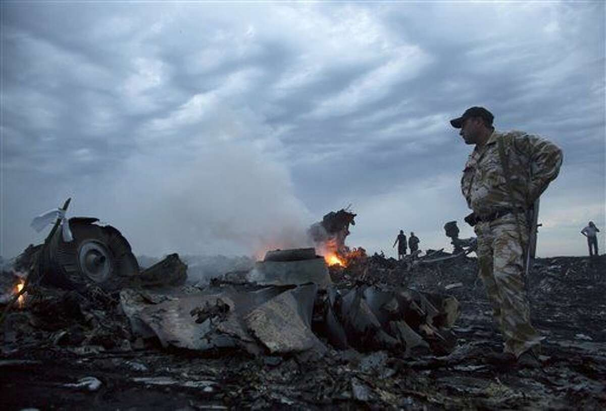 FILE - In this July 17, 2014 file photo people walk amongst the debris, at the crash site of a passenger plane near the village of Grabovo, Ukraine. The Dutch Safety Board is publishing its final report Tuesday, Oct. 13, 2015 into what caused Malaysia Airlines Flight 17 to break up high over Eastern Ukraine last year, killing all 298 people on board. (AP Photo/Dmitry Lovetsky, File)
