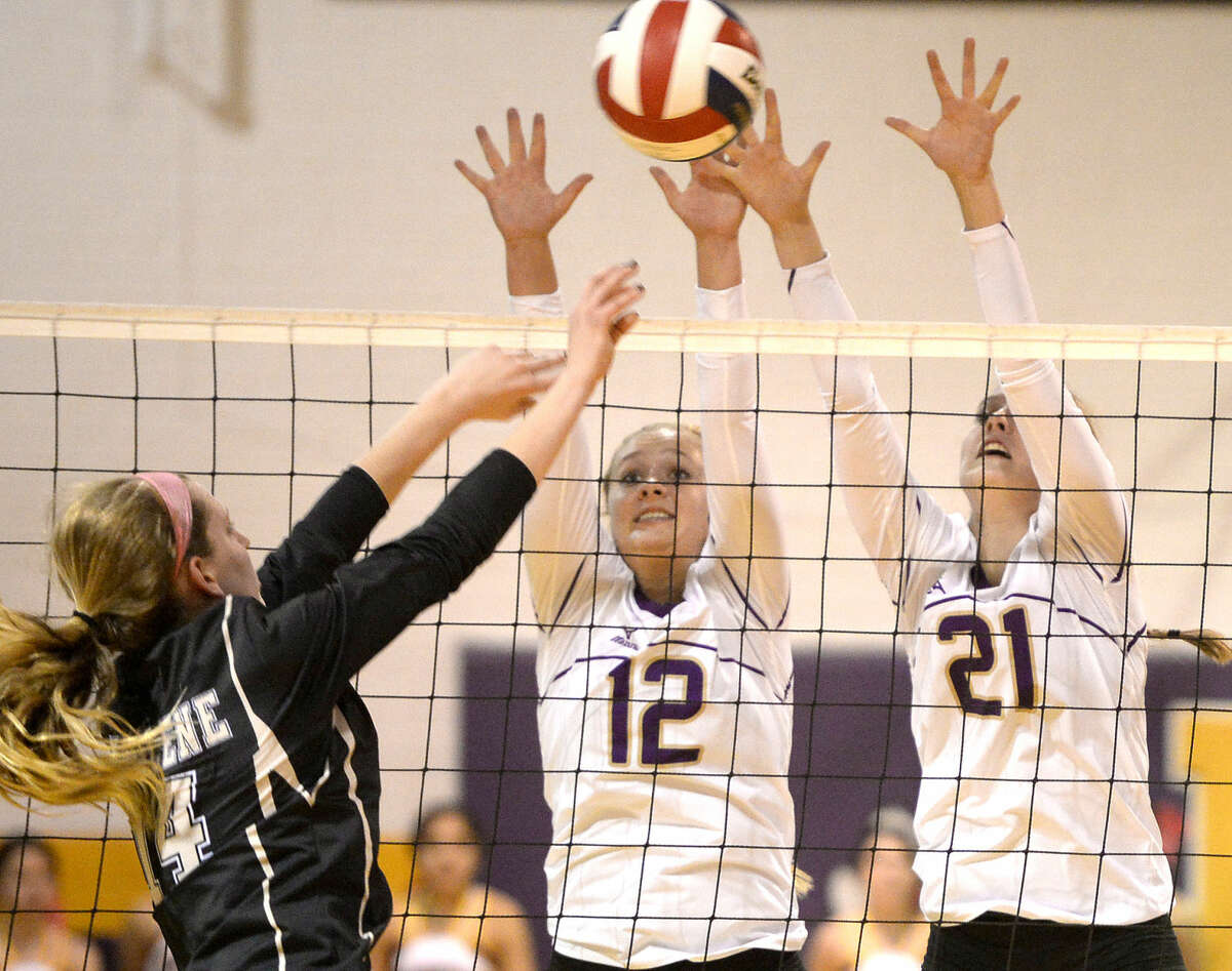 Midland High right side Christen Beckham (12) and middle hitter Krista Epley (21) try to block a hit from Abilene High's Hannah Tawney (14) on Tuesday, Oct. 13, 2015 at Midland High. James Durbin/Reporter-Telegram