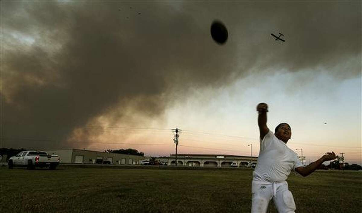 Matthew Maldonado, 10, plays catch with his brother, Gabriel, 12, Tuesday, Oct. 13, 2015, in Smithville, Texas, as a single engine air tanker plane begins to make it's drop run overhead towards the Luecke wildfire. (Rodolfo Gonzalez/Austin American-Statesman via AP) AUSTIN CHRONICLE OUT, COMMUNITY IMPACT OUT, INTERNET AND TV MUST CREDIT PHOTOGRAPHER AND STATESMAN.COM, MAGS OUT; MANDATORY CREDIT