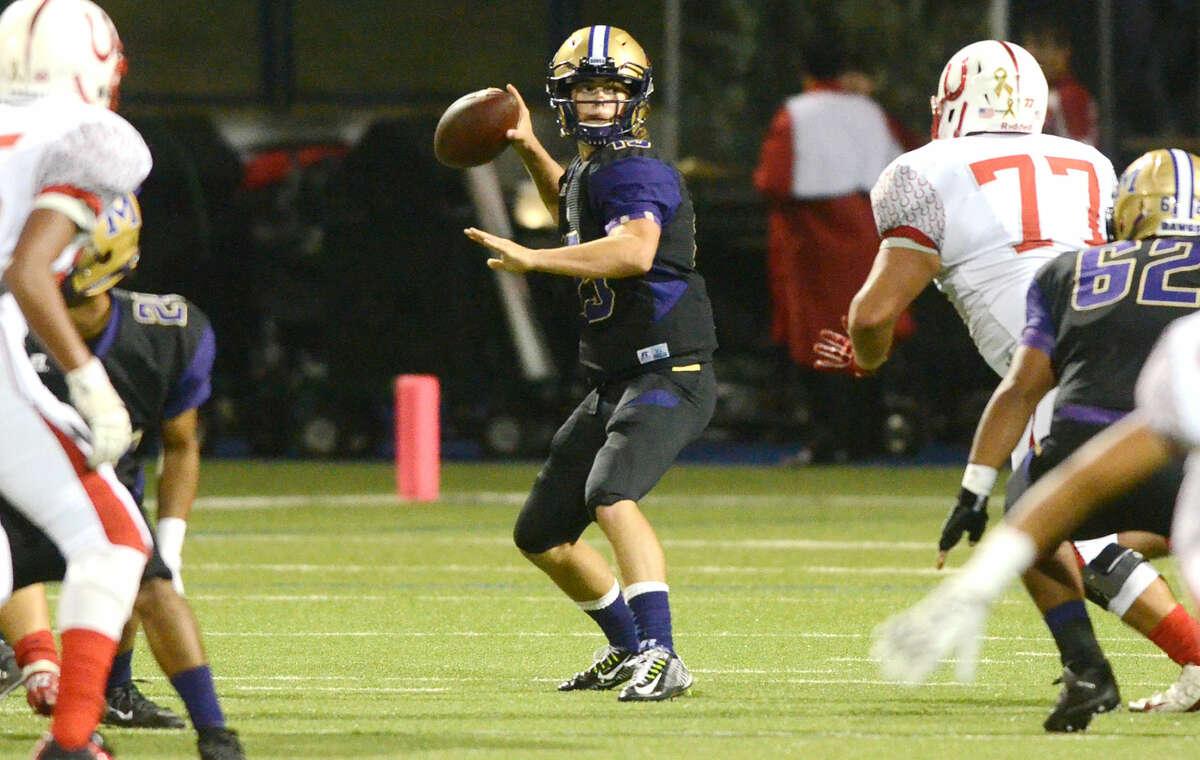 Midland High quarterback Jackson Anuszkiewicz (15) looks to make a pass while under pressure from Odessa High's Raymond Rodriguez (77) on Friday, Oct. 9, 2015, at Grande Communications Stadium. James Durbin/Reporter-Telegram