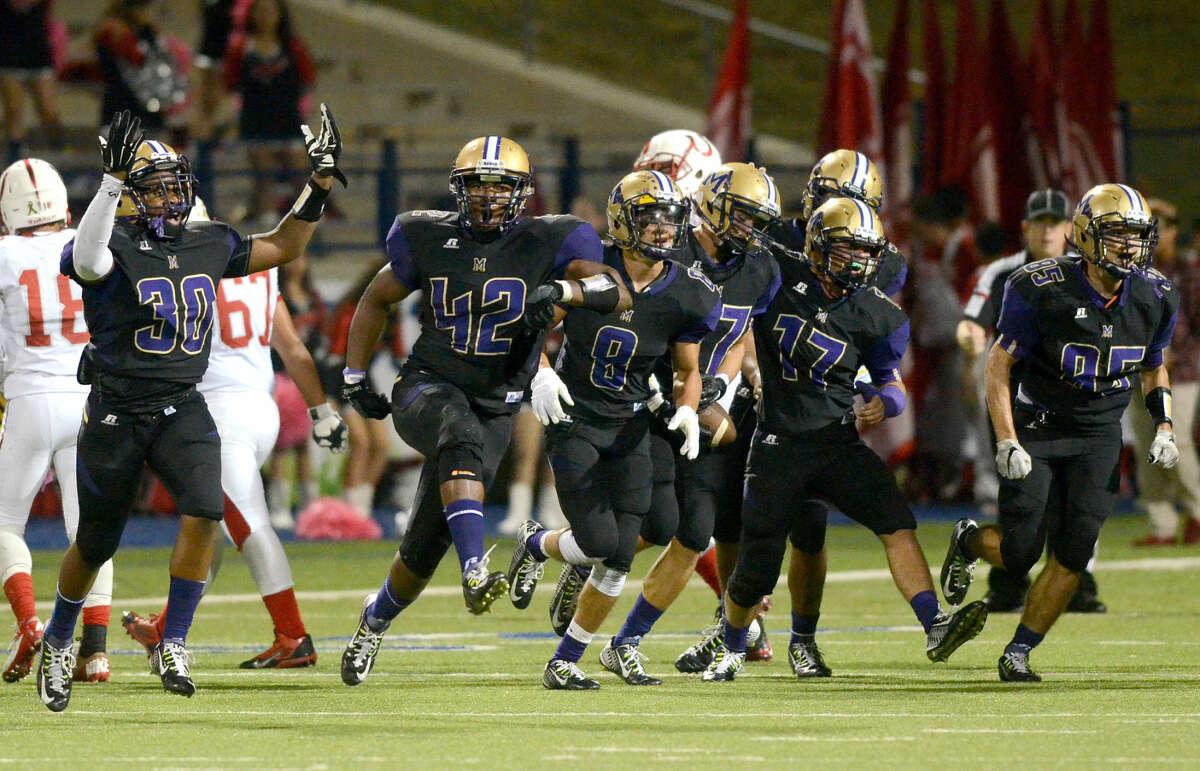 The Midland High defense celebrates after Chris Sims' interception against Odessa High on Friday, Oct. 9, 2015, at Grande Communications Stadium. James Durbin/Reporter-Telegram
