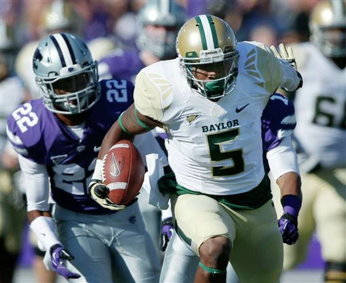 Baylor wide receiver Antwan Goodley (5) runs with a reception for a touchdown as Kansas State defensive backs Randall Evans, obscured, and Dante Barnett (22) pursue, during the first half of an NCAA college football game in Manhattan, Kan., Saturday, Oct. 12, 2013. (AP Photo/Orlin Wagner)
