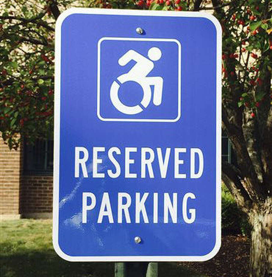 In this Friday, Sept. 25, 2015 photo provided by Favarh, The Arc of the Farmington Valley, a modernized handicapped sign designates a reserved space in a parking lot in Canton, Conn. Advocates want to replace the familiar image of a stick figure in a wheelchair with the action-oriented logo to emphasize ability, not disability. (Bill Neagus/Favarh, The Arc of the Farmington Valley via AP) Photo: Bill Neagus