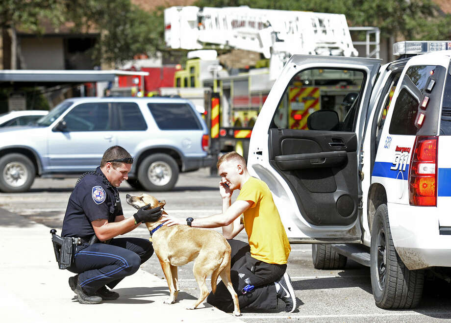 Midland Police Department officer Tyler Thompson returns a dog named Leo to his owner, Austen Lawler, after the animal was rescued by Midland firefighters from an apartment fire at The Annex apartments on Friday, Oct. 16, 2015. James Durbin/Reporter-Telegram Photo: James Durbin