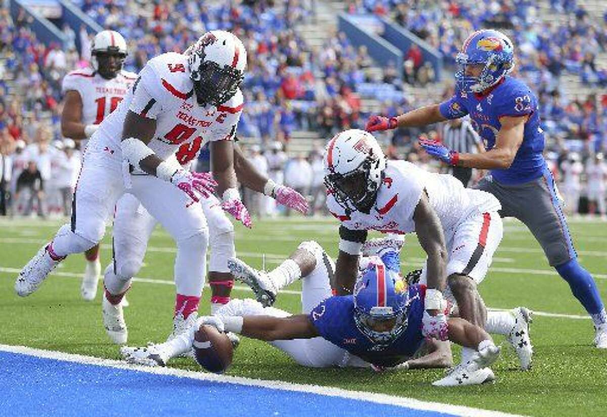 Kansas wide receiver Darious Crawley reaches the ball across the goal line for a touchdown as he is defended by Texas Tech defensive back J.J. Gaines (3) and defensive lineman Branden Jackson (9) during the second half Saturday, Oct. 17, 2015, at Memorial Stadium in Lawrence, Kansas. (Nick Kruf/The Journal-World via AP)