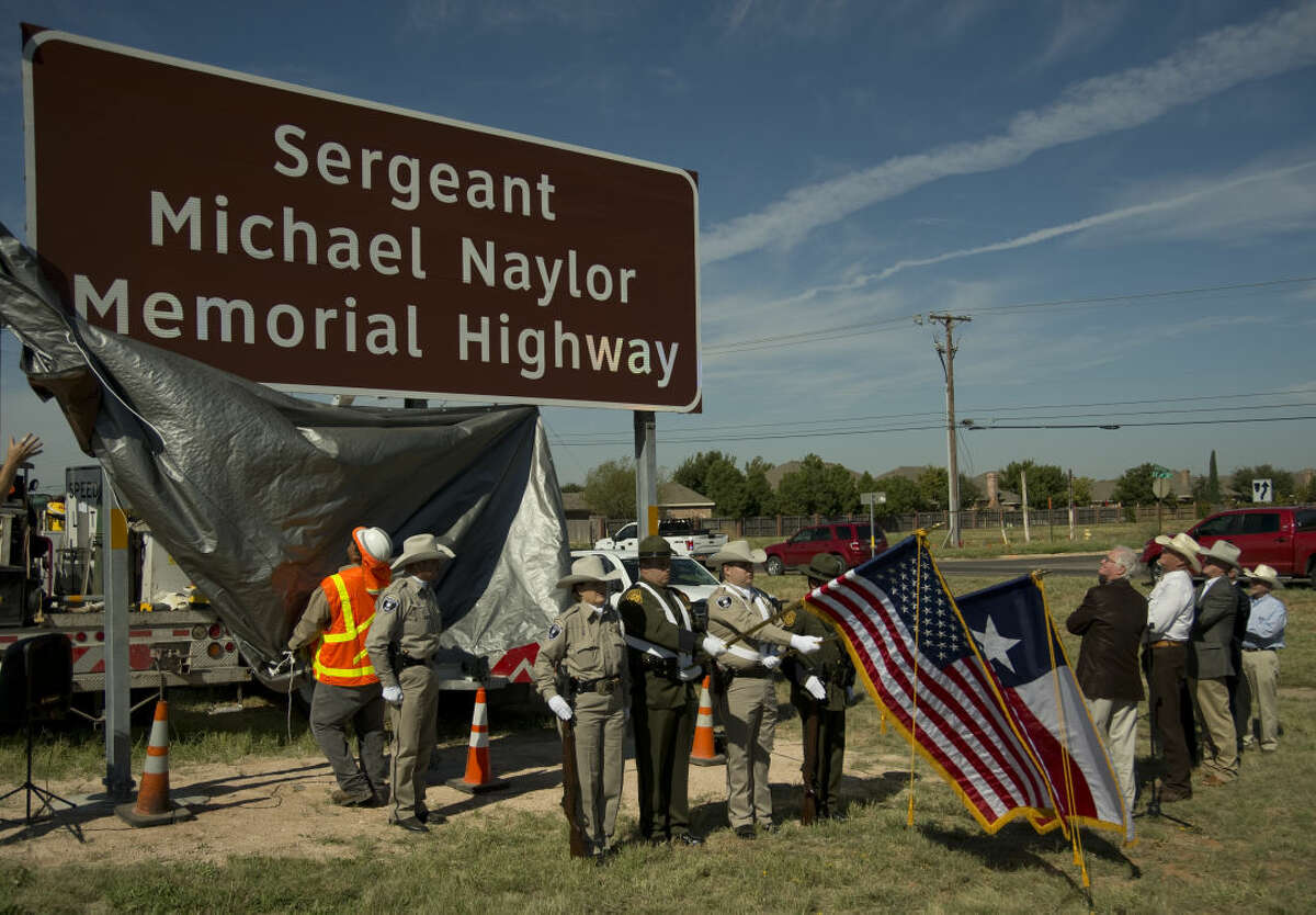 Midlanders watch as the newly dedicated marker on Hwy 191 just west of Loop 250 Thursday 10-15-2015 of the Sgt. Michael Naylor Memorial Highway sign is unveiled. Tim Fischer\Reporter-Telegram