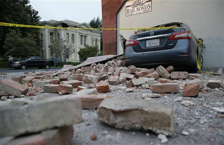 People walk past a tumbled mannequin and broken storefront window on First Street following an earthquake Sunday in Napa, Calif. (Associated Press/Eric Risberg) Photo: Eric Risberg
