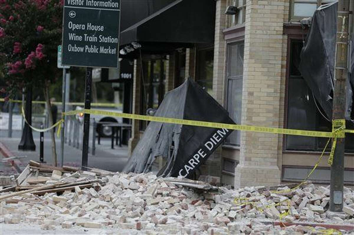 Bricks and rubble cover the sidewalk in front of a heavily damaged building following an earthquake Sunday in Napa, Calif. (Associated Press/Eric Risberg)