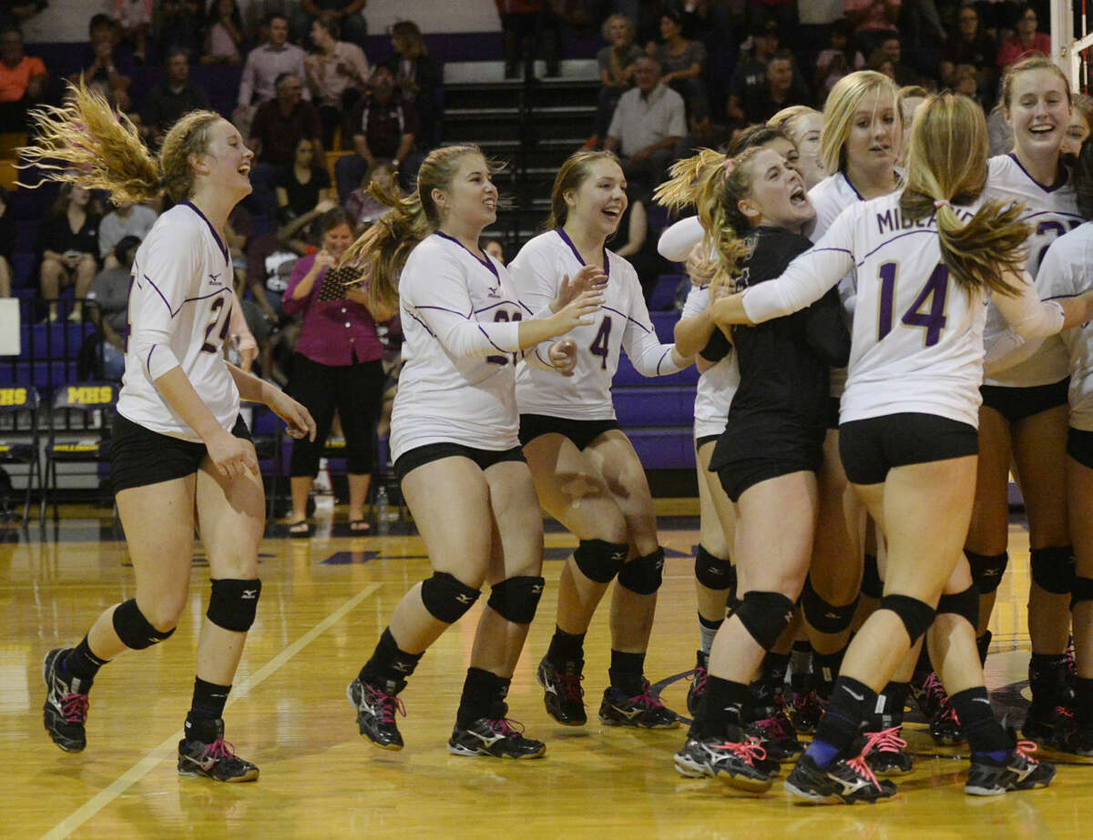 Members of the Midland High volleyball team celebrate a win against Lee High on Tuesday, Oct. 20, 2015, at Midland High. James Durbin/Reporter-Telegram