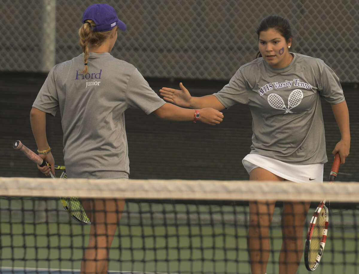 Sofia Salcedo, right, and doubles partner Ellie Hord slap five after winning a point Tuesday 10-20-2015 at the District 3-6A/4-6A Tournament. Tim Fischer\Reporter-Telegram
