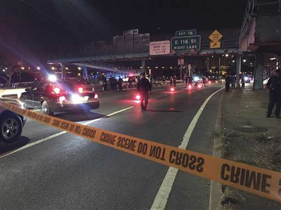 Police officers investigate along FDR Drive at East 120 Street on Tuesday, Oct. 20, 2015, in New York where a New York City police officer was fatally shot. Officer Randolph Holder, 33, died after being shot in the head in a gun battle while pursuing a suspect following a report of shots fired, police said. (AP Photo/Michael Balsamo) Photo: Michael Balsamo