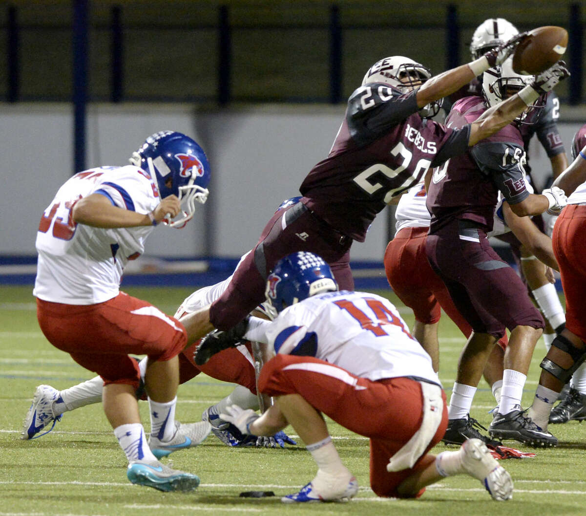 Lee High defensive back Garrett Chalker (20) blocks a kick from Abilene Cooper's Pedro Lira (39) and Stetson Hodges (14) and went on to recover the ball for a turnover Friday, Sept. 25, 2015, at Grande Communications Stadium. James Durbin/Reporter-Telegram