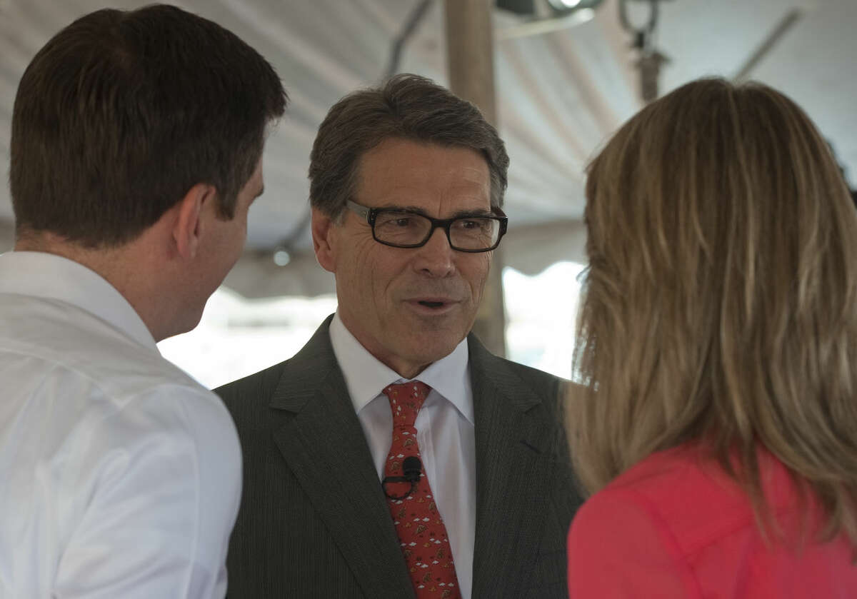 Gov. Rick Perry talks with Brooks and Shelby Landgraf Tuesday morning during the ground breaking ceremony for OXY Midland Office Complex. Tim Fischer\Reporter-Telegram