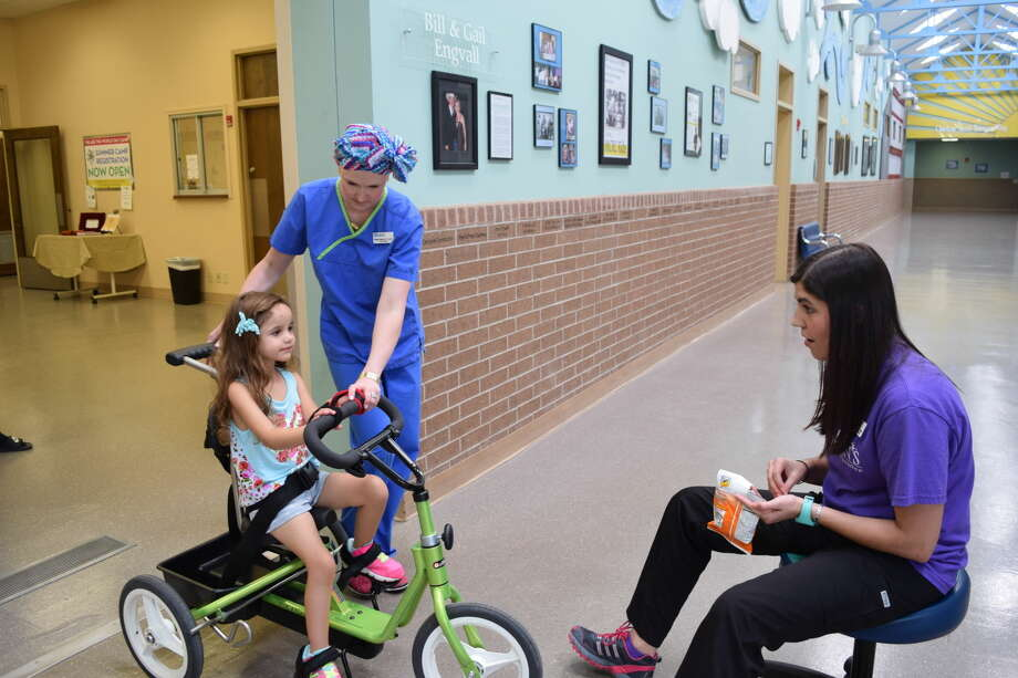 Emme Valenzuela works with her therapists Morgan Pistocco and Juliana Wright, seated. A specially-adapted bike allows Emme to ride and participate in the upcoming Basin Bikefest. Photo: Courtesy Photo