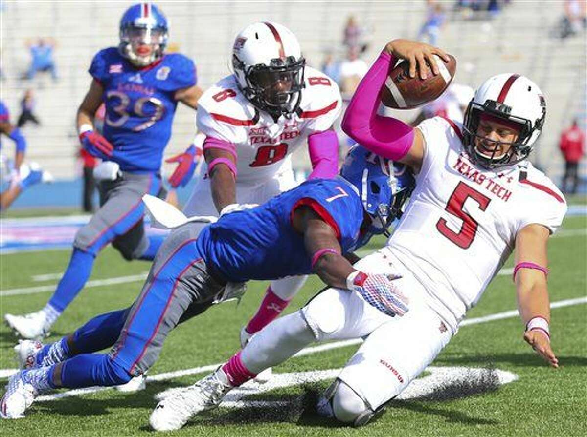 Texas Tech quarterback Patrick Mahomes (5) is hit by Kansas defensive back Derrick Neal (7) during the second half of an NCAA college football game on Saturday, Oct. 17, 2015, in Lawrence, Kan. Texas Tech won 30-20. (Nick Kruf/The Journal-World via AP)