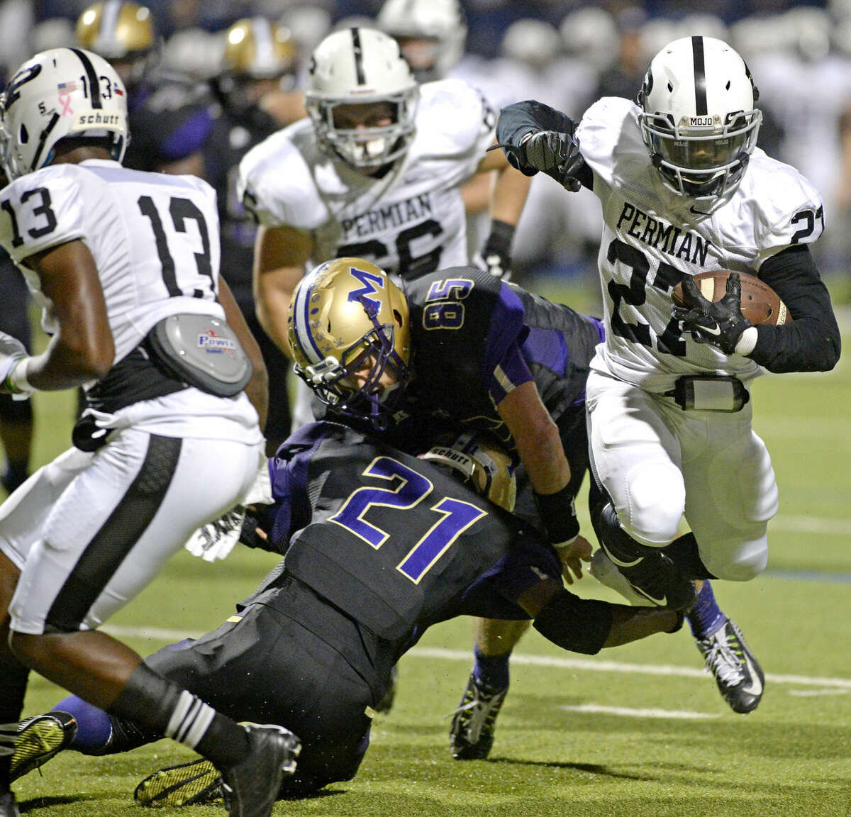 Midland High cornerback Raekwon Anderson (21) and linebacker Jack Youngblood (85) get tangled up with each other as Permian's Brandon Bailey (27) blasts past for a touchdown Friday, Oct. 23, 2015, at Grande Communications Stadium. James Durbin/Reporter-Telegram